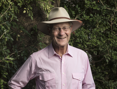 Smiling portrait of Tim Fairfax AC, standing outdoors, wearing an akubra hat.